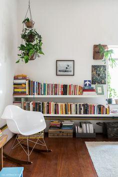 Estante feita com prateleiras suspensas, livros coloridos e muitas plantas ao redor