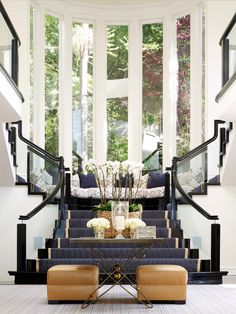 What a unique look... Amazing! Black white and gold. tall windows. symmetrical staircase.