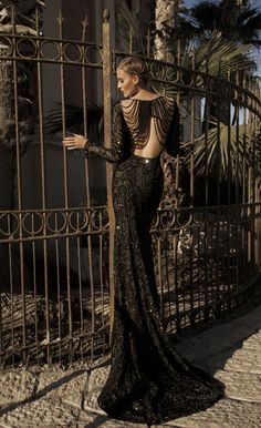 Entirely embroidered in jet-black glass beads that layer over sheer net with draping of black pearls.