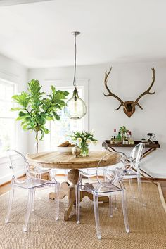 Cloud Whiteby Benjamin Moore creates aseamless and expansive feel in this dining room - love the antlers & bar tray    Dining room:A round table eases traffic flow...