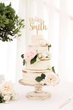02 semi naked three-tiered wedding cake with fresh flowers and a calligraphy topper - Weddingomania