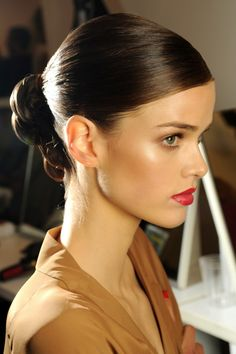 Slick back bun - gel hair slick into a mid-height ponytail, plait (braid) and voila! The more shine the better, so serum or gel would work well.