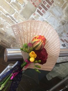 Fan bouquets. We used fans and flowers similar to my bridesmaids  bouquets, tied with lace ribbon to add to the theme and decorate the venue room.