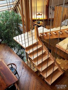The open staircase, which has spalted-maple treads suspended on steel rods, adjoins an indoor garden and connects the house's three floors. Photography by Eric Laignel.