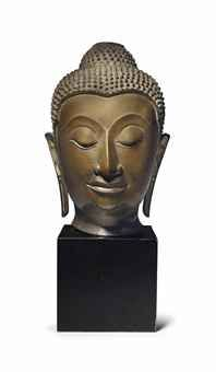 A bronze head of Buddha  Thailand, Ayutthaya, circa 16th century  Very finely modeled with serene expression with gentle smile, downcast eyes, and finely arched brows, the hair in tight curls over the prominent ushnisha, with remains of gilding 12 in. (30.5 cm.) high