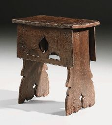 AN OAK BOARDED STOOL  English, 16th Century  With later top, the aprons pierced with a triform Gothic motif, the ends extending to feet and with butressed edges, one frieze branded 'IS'