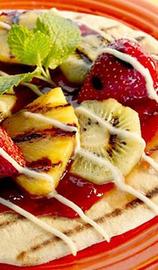Grilled Fruit Pizza - A neat twist on the old pepperoni pizza! Delight guests with their own hot-off-the-grill dessert pizza. Choose between white and dark chocolate, then add your favourite fruits; a hot grill blends it all together.