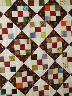 Scrappy quilt pattern using neutral backgrounds with nine patch scrap blocks.