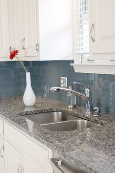 Installing a peel and stick backsplash in your kitchen with glass tiles in a subway pattern. It makes a beautifully modern look to the kitchen.