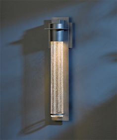 This tube of glowing light from Hubbardton Forge will give a unique glow through its seeded clear glass. You can count on this fixture rain or shine, as it is an outdoor piece compliant even in wet weather. See it in our showroom, or call and speak with a sales representative to learn more.