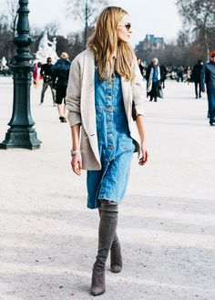 A button-down denim dress is worn with a neutral sweater and knee high suede boots