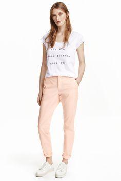 Spodnie chinos: Spodnie chinos z elastycznej, spranej bawełny. Kieszenie po bokach, z tyłu kieszenie z guzikiem. Wąskie, zwężane nogawki.