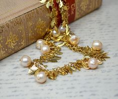 Pale blush pearl drop necklace Shimmering gold leaf chain necklace Elegant pearl dangle necklace Spring summer fashion statement jewelry