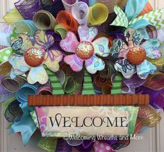 This colorful deco mesh Welcome wreath will look bright and sunny on your door this Spring and Summer! This wreath measures 24 in diameter with a depth of 8. The wreath is constructed out multiple colors of deco mesh. Wired ribbons adorn all sides of the wreath. The large tin