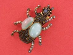 """Incredible Ornella beetle brooch. Similar one was featured in the """"Jewels of Fantasy"""" by Deanna Farneti Cera (just had different cabochons) - page 263. Gold tone setting with large green cats eye cabochons, large green rhinestone head, and body covered by tiny green Aurora Borealis beads and legs adorned by Aurora Borealis rhinestones. 