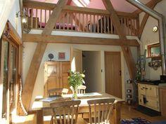 Oak frame house in woods in Devon, UK. By Roderick James Architects