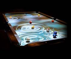Play billiards on this digitally upgraded pool table that interacts with every movement of the pool balls. Custom set high definition imagery displays underneath each ball, and more of the image gets revealed as the pool balls roll over this high class pool table.