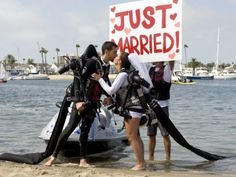 Newlyweds Grant Engler, 25, and, Amanda Volf, 26, both of Grand Rapids, Michigan kiss a water-powered jetpack wedding in Newport Bay Thursday afternoon. The wedding, put on by ZOZI with jetpacks from Jetlev Southwest was purportedly the world's first wedding by water-powered jetpack. PHOTO BY LEONARD ORTIZ, THE ORANGE COUNTY REGISTER