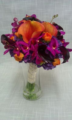 Rich purple and burgundy tones are brightened with hints or orange in this Wedding bouquet... mini calla lilies, mokara orchids, ranunculus and dutch hydrangea are used.