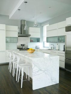 White kitchen with dark floors.