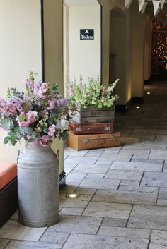 Milk churns and crates with flowers