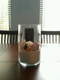 Table centerpiece with sand, seashells, and candle.