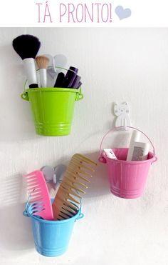 Ganchos + cachepôs de baldinhos perto do espelho criam uma organização vertical de maquiagem e acessórios de beleza.