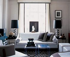 living rooms - white black silk Greek key pillows white sofa white black geometric rug silver. stacked ball lamps lucite acrylic tables white fabric cornice box white drapes black ribbon trim turquoise blue table white leather square ottomans gray walls paint color living room
