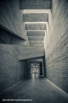 Mostyn Gallery - The new 'tube' atrium links all the parts of the gallery. A dramatic canyon of board-marked concrete, spanned by a faceted bridge, this space establishes an exuberant atmosphere of expectation.