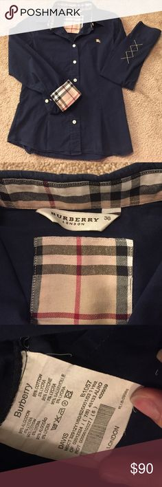 Burberry long sleeve button up! Beautiful gently worn Burberry long sleeve button up! Dark navy blue base color with Burberry trademark pattern on the inside of the collar and sleeves. Ribbon banner burberry on back bottom right of shirt. Burberry logo on front left chest of shirt. Hint of argyle on bottom of left sleeve right before the main wrist cuff. IT size 36; equivalent to US size 2. Smoke free home. Burberry Tops Button Down Shirts