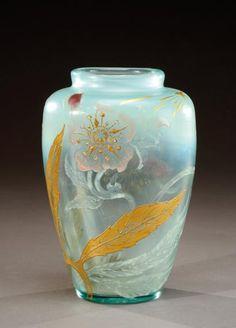 Emile Gallé (1846-1904)  Vase à corps de forme ovoïde et col étranglé droit en verre teinté vert d'eau à décor de motifs floraux dégagés à l'acide, émaillés et rehaussés de dorure dans les tons mauve, rose et doré. Signé sous la base « Gallé déposé ». Vers 1884.  H: 20 cm