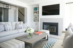 Beach cottage living room features a beadboard ceiling over a pair of matching ivory sofa facing each other across from a Restoration Hardware Martens Rectangular Coffee Table flanked by beige stripe poufs atop a turquoise chevron rug.