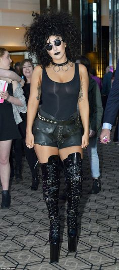 All-black beauty: The star rocked patent boots with stirrup hot pants, slipping a see-through vest on but choosing not to wear a bra