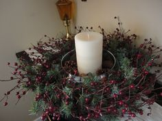 This is made from the base of a hanging candelabra. I removed all attached iron polls and placed greenery and berries inside the iron base. I set a large shallow bowl in the center and put a large candle in the middle of it.  I then placed tiny pinecones and acorns around the candle.  It is a beautiful display on my hope chest.  It also looks great on an end table or in the center of our dining table