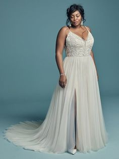 Plus size wedding dress by Maggie Sottero - CHARLENE LYNETTE, This chic A-line offers additional coverage to this bridal gown, featuring a bodice accented in beaded lace motifs, Swarovski crystals, and sheer side insets atop a voluminous tulle skirt. Beaded spaghetti straps complete the V-neckline, trimmed in illusion, and V-back.  #weddingdress #weddingdresses #bridalgown #bridal #bridalgowns #weddinggown #bridetobe #weddings