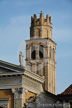 Tower of a church with stone angels in Conegliano, Italy.