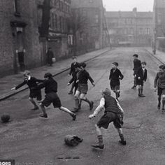 Boys playing football in the road without a care in the world... Those were the days...