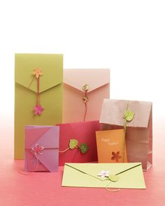 Cut from card stock using specialty craft punches, these botanical embellishments are an easy way to spruce up envelopes and gift bags. Sew the fasteners on with silk beading cord, and double-knot on the back. Then wind a length of cord in a figure eight to close. Or simply wrap the cord around an envelope or bag, and secure with a single bud.