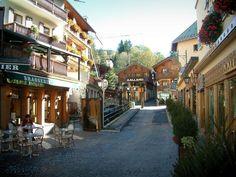 Megève: Café terrazza, piccolo ponte sopra il fiume, negozi e case del paese (stazione di sport invernali ed estivi) - France-Voyage.com
