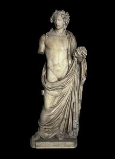 Marble statue of the wine-god Dionysos; holding a bunch of grapes. His head is wreathed with vines and his sandals are decorated with ivy-leaves. Roman.