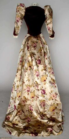 "velvet & silk reception gown, Paris, c. 1894 2 piece cranberry velvet & watered rose print on ivory satin, bodice w/ CF & CB waistpoints, brussels lace collar & cuffs, petersham label, ""A. Felix, Brevete, Paris"", 17 stamped brass buttons, trained skirt"
