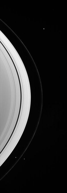 Three Little Moons: Three of the small worlds that hug the outer edges of Saturn's immense ring system are captured in this Cassini spacecraft portrait.