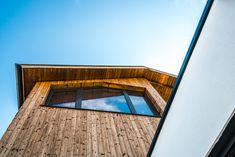 Die Fassadengestaltung des Einfamilienhauses zeichnet sich durch die Ausrichtung der Fenster aus, welche an die Ausblicke auf die umliegende Berglandschaft angepasst ist. Das Haus spiegelt dadurch eine Transparenz wieder, was der Idee eines offenen Lebensstils und einem gefühlvollen Umgang mit der Natur nahekommt. Im Herzen des Hauses werden alle Stockwerke durch eine offene Deckenkonstruktion miteinander verbunden, was im Innenraum ein Atrium entstehen lässt. Atrium, Architecture, Stairs, Exterior, Mansions, House Styles, Design, Home Decor, Decorations