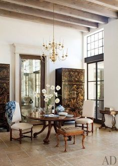 Chinese lacquer cabinets flank a mirrored pocket door that leads from the salon's dining area to the kitchen in Rela Gleason's Napa Valley home. The table, set with heirloom Canton china, is by Studio Workshops, and the 19th-century English chairs are upholstered in a Summer Hill linen | archdigest.com