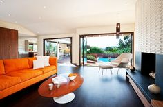 Comfortable Mid century Living Room with Orange Sofa and Wooden Oval table on Darkwood Floor and Modern Fireplace Design Idea : Inspirational Interior and Exterior Home Design Ideas – TheMakaroni.com