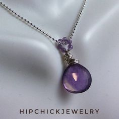 "Lovely hand-faceted genuine amethyst gemstone; shaped in a briolette. It has been intricately wire wrapped in Sterling Silver to form a pendant. Unlike other Artisans on the market I have used 2 millimeter size amethyst round beads to form the necklace bail.    Your pendant hangs off a 925 sterling silver chain measuring 16"" inches. Pendant length is 1.25 inches.    Each HipChickJewelry purchase comes in a classic coffee and cream colored gift box, perfect for gift-giving or home storage…"