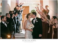 Bride and groom kiss outside of the wedding ceremony with sparklers - bridal party picture ideas