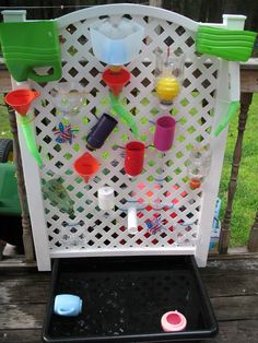 Water wall. From Lowe's I purchased the piece of vinyl gate, clear tubing and trough at the bottom. Walmart had the cheap funnels and zip ties. The bottles, pit balls and pinwheels were recycled from home. Idea from http://familylicious.com/water-wall-ball-run/