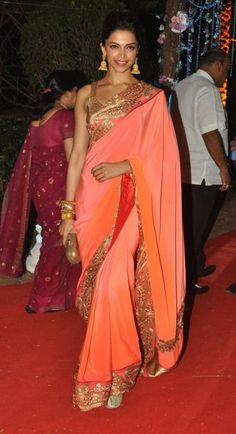 Deepika Padukone attended Ahana Deol and Vaibhav Vohra's wedding reception in a classy peach and gold saree by the designer duo, Monica and Karishma . The gorgeous lady of Bollywood completed her look with the jewellery from Amrapali. - bollywoodshaadis.com