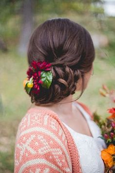 Lovely updo adorned with cranberry-colored flowers | Photo by Blackbird Photography and Design